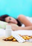 Mulher doente na cama e nos comprimidos Fotos de Stock Royalty Free