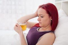 Mulher doente nova com o copo do chá Fotos de Stock Royalty Free