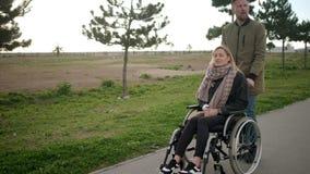 A mulher doente nova está sentando-se na cadeira de rodas, o homem está ajudando a e o rolamento video estoque
