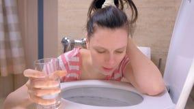 A mulher doente nova está vomitando no toalete que senta-se no assoalho no vidro de água do homewith à disposição, sintoma da int video estoque