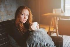 Mulher doente nova que cura com bebida quente em casa no sofá acolhedor imagem de stock