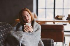 Mulher doente nova que cura com bebida quente em casa no sofá acolhedor foto de stock