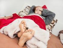 Mulher doente nova que encontra-se na cama Imagem de Stock Royalty Free