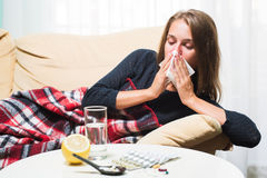 Mulher doente que encontra-se no sofá sob o nariz espirrando de lãs e de limpeza geral Imagem de Stock Royalty Free