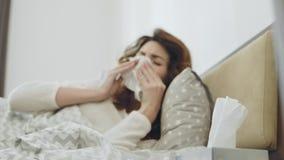 Mulher doente que obtém o vírus da garganta que encontra-se na cama Mãos fêmeas do close up que tomam o guardanapo video estoque