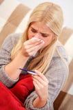 Mulher doente que olha o termômetro Fotografia de Stock Royalty Free