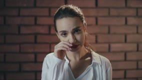 Mulher doente que toca na garganta inflamada e no nariz durante uma doença fria no estúdio do tijolo vídeos de arquivo