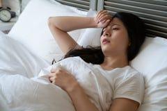 A mulher doente sofre a dor de cabeça com mão na testa imagens de stock royalty free