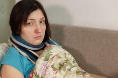 Mulher doente triste nova que encontra-se na cama em casa imagens de stock