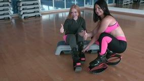 A mulher dois bonita em sapatas do kangoo mostra os polegares acima no gym vídeos de arquivo