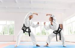 Mulher dois desportiva que luta no treinamento do karaté na escola de artes marciais foto de stock
