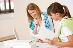 Mulher dois do estudante em casa - com livro e portátil Fotografia de Stock Royalty Free