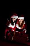 Mulher dois no presente do Natal da abertura do traje de Santa. fotografia de stock