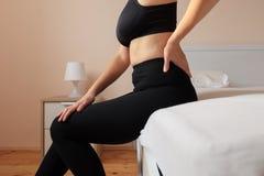 A mulher dolorosa está sentindo a dor lombar no quarto imagem de stock royalty free