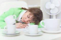A mulher dorme na tabela entre copos de café Imagens de Stock Royalty Free