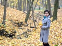 A mulher dos anos médios custa com as folhas de bordo amarelas nas mãos Imagem de Stock