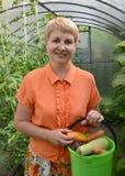 A mulher dos anos médios guarda à disposição uma cubeta com vegetais Foto de Stock Royalty Free