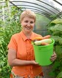 A mulher dos anos médios guarda à disposição uma cubeta com vegetal Fotos de Stock