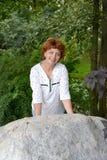 A mulher dos anos médios inclina as mãos contra um pedregulho Fotografia de Stock