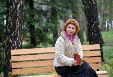 A mulher dos anos médios senta-se em um banco com as folhas de bordo do outono nas mãos Fotografia de Stock