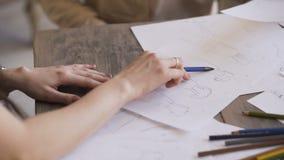 A mulher dos desenhistas de Clother cria um esboço no close up de papel no estúdio do alfaiate