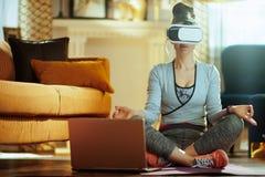 Mulher dos esportes com o portátil na engrenagem de VR que medita na casa moderna imagem de stock