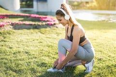 Mulher dos esportes que faz exercícios do gramado e que estica amarrando os laços exteriores fotos de stock