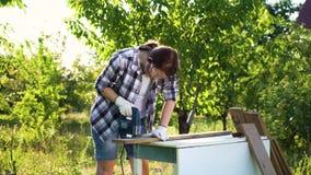 A mulher dos ofícios não corta a prancha de madeira com serra de vaivém e joga luvas no desespero vídeos de arquivo