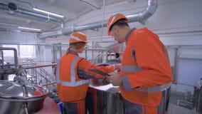 A mulher dos operários com o homem nos capacetes com portátil da tabuleta está verificando a planta de produção ao discutir a qua filme