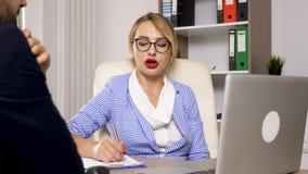 Mulher dos recursos humanos que toma notas e que fala com um canditate para o trabalho novo video estoque