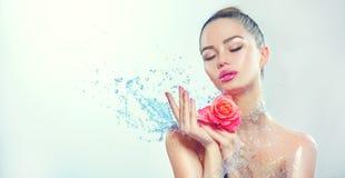 Mulher dos termas A menina de sorriso da beleza com espirra da água e aumentou em suas mãos imagem de stock royalty free
