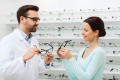 Mulher e ótico que mostram vidros na loja do sistema ótico foto de stock royalty free