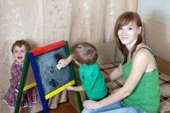 A mulher e as crianças desenham no quadro-negro imagens de stock