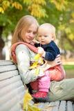 Mulher e bebê bonito com as folhas que sentam-se no banco Foto de Stock Royalty Free