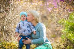Mulher e bebê felizes na floresta de florescência da mola com alecrins foto de stock royalty free