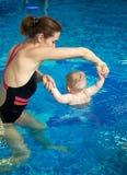 Mulher e beb? que fazem os exerc?cios que flutuam na posi??o ereta na associa??o rasa Preven??o do endurecimento e da doen?a Vist imagens de stock