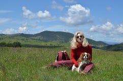 Mulher e cão que jogam no prado Imagens de Stock Royalty Free