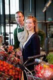 Mulher e caixeiro do supermercado foto de stock