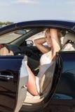 Mulher e carro consideravelmente louros do luxo Imagens de Stock Royalty Free