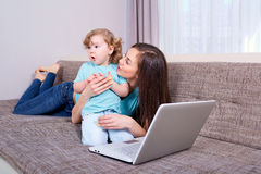Mulher e criança felizes da família com um portátil no sofá em casa Imagens de Stock Royalty Free