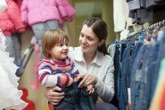 A mulher e a criança felizes escolhem calças de brim Fotografia de Stock