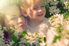A mulher e a criança felizes na mola de florescência jardinam foto de stock