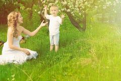 A mulher e a criança felizes na mola de florescência jardinam fotos de stock