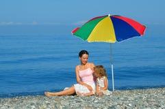 A mulher e a criança na praia Imagem de Stock