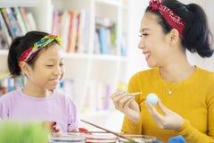 Mulher e criança que decoram ovos da páscoa em casa imagens de stock