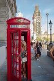 Mulher e criança que retiram uma cabine de telefone tradicional vermelha em Lon imagens de stock royalty free