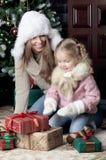 Mulher e criança que sentam-se perto da árvore de Natal Imagens de Stock