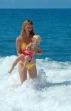 A mulher e a criança têm o divertimento no mar Fotografia de Stock Royalty Free