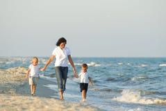 Mulher e crianças na praia Fotografia de Stock Royalty Free