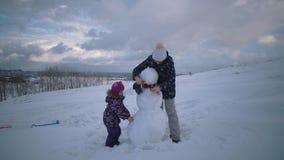 A mulher e a crian?a esculpem junto um boneco de neve no monte vídeos de arquivo